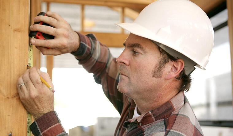 Residential construction worker taking measurements