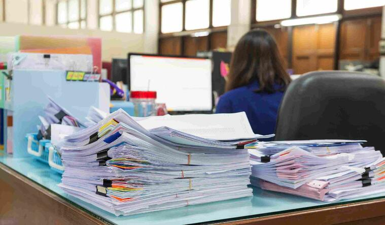 Pile of paperwork on an office desk